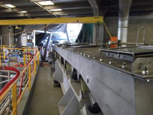 Vibrating chemical conveyor on site.