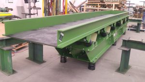 Vibrating feeder with mild steel liners and rubber sound deadening.